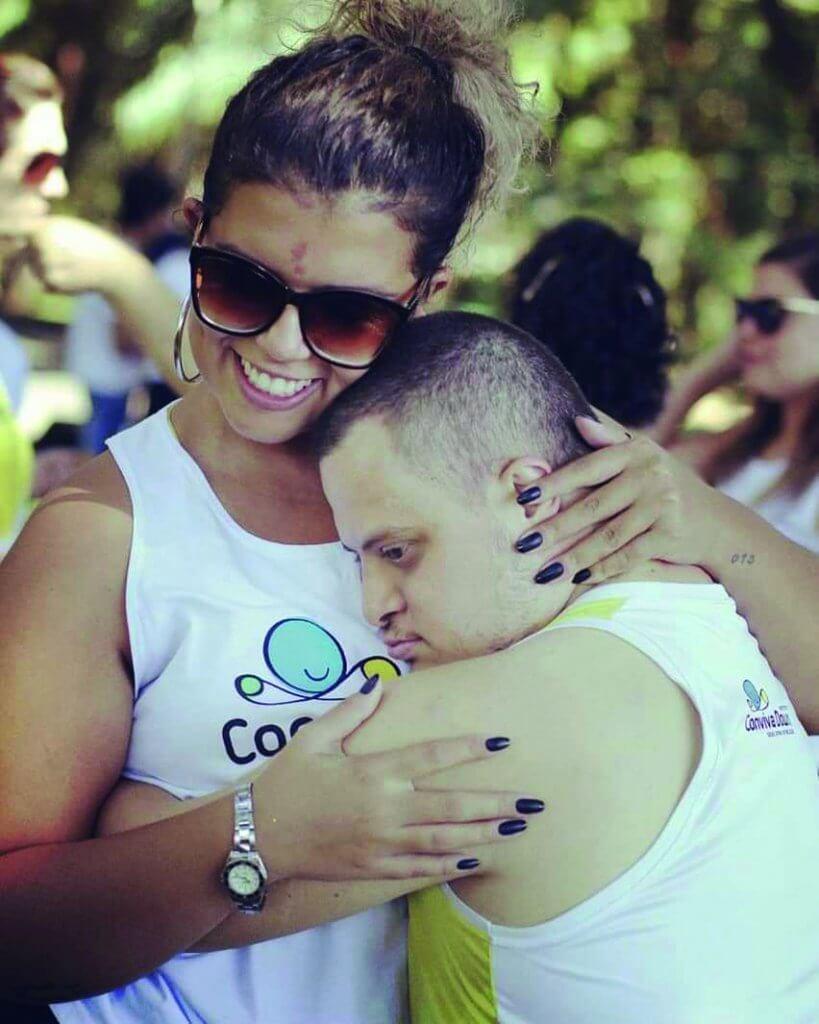 Camila abraça seu alun com sindrome de Down